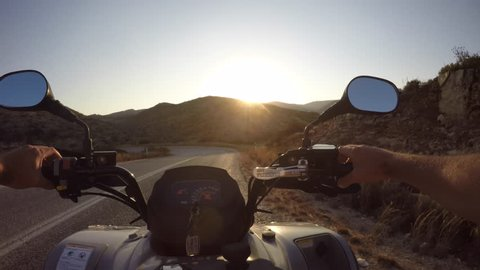 Perspective shot driving a quad motorcycle across a road in the hills of the Greek island of Paros. Golden hour early evening light.