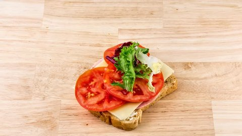 making sandwich bread with tomato, ham, cheese and salad stop motion. preparing snack. stop motion, top view. 4K