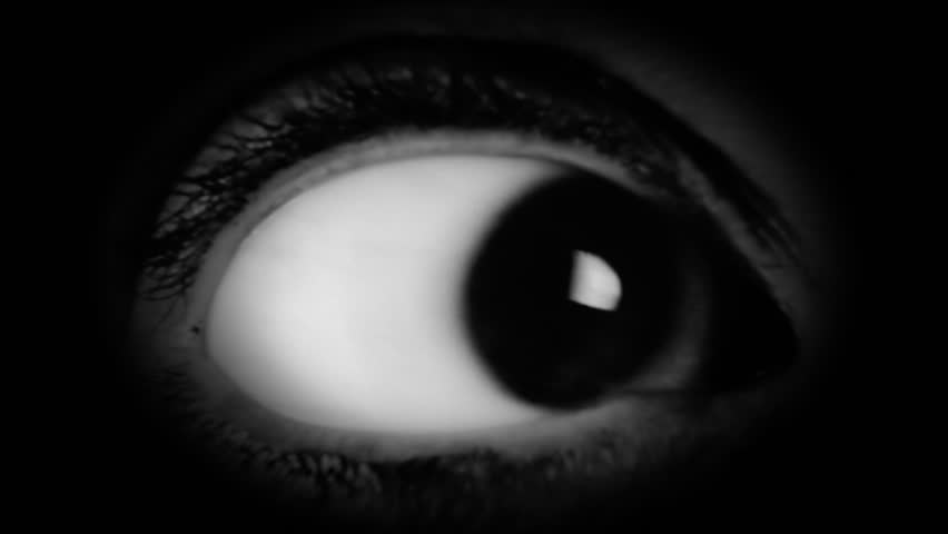 The big eye of a woman, looking in camera, scared. Film-noir style. Detail macro shot.