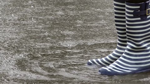 Close up person in gumboots, wellingtons or rubber boots jumping outdoor in puddle of water in rainy wet weather, raindrops splashing, spraying, slow motion.