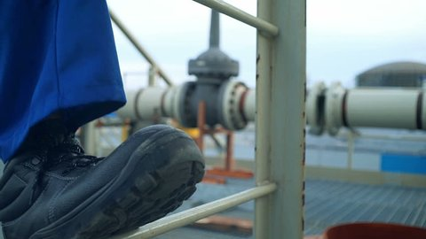 ?ngineer feet climbing the tower of a large oil refinery. Close-up