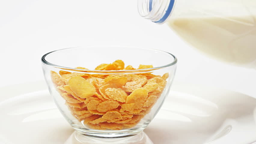 Corn flakes in a glass bowl pouring with milk over white