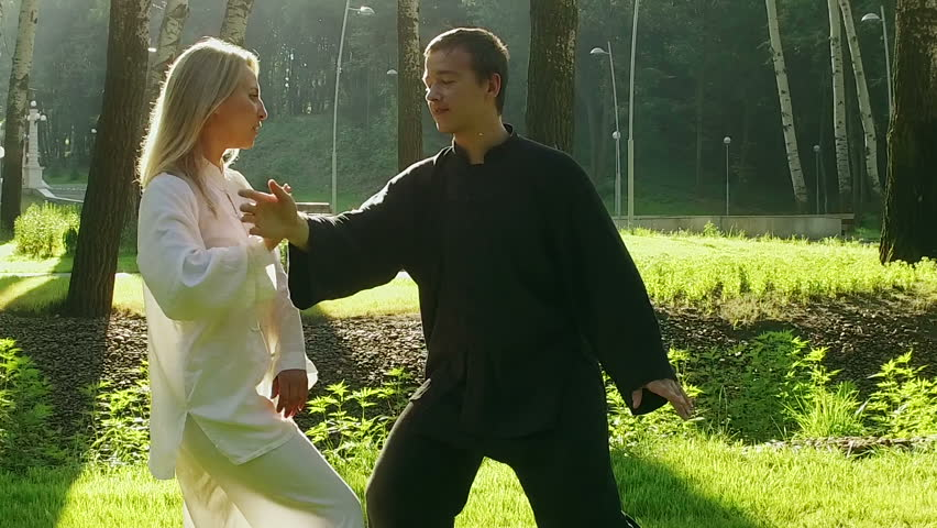 Training in the park. Workout. Blond woman and young man practicing elements of qigong. Slow motion. HD | Shutterstock HD Video #19230487