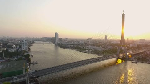 Drone Shot Rama 8 bridge crossing chaopraya river in heart of bangkok thailand capital important traveling destination , Sunet time.