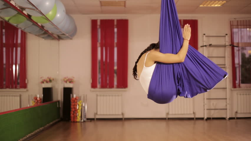 Anti-gravity Yoga, athletic woman doing yoga exercises indoor   Shutterstock HD Video #19246207