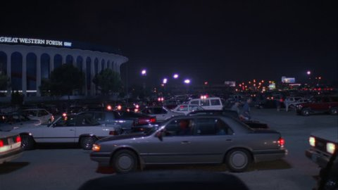 night pan left across full parking lot cars leaving along Great Western Forum LA forum, indoor arena House Lakers basketball team from 1967 1999 , concert venue font color red Needs additional clear