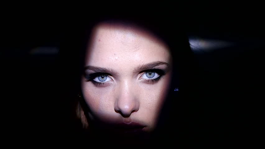 Pretty brunette woman with blue eyes artistic portrait looking into the camera with shadows on her face