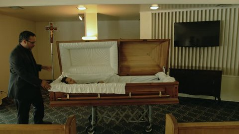 Dead man lays in the coffin. Other guy does a preparation before burial.