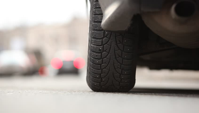 Rear tyre of starting car, vehicle begin to move, environment road noise. Low camera position, studded tire of standing car. Left rear wheel view, auto ride away, rendered in blur at distance. | Shutterstock HD Video #19300894