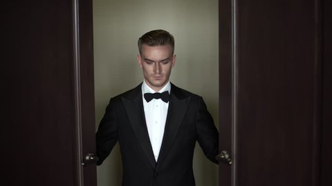 Scary man in a tuxedo and bow tie opens the door. Intro