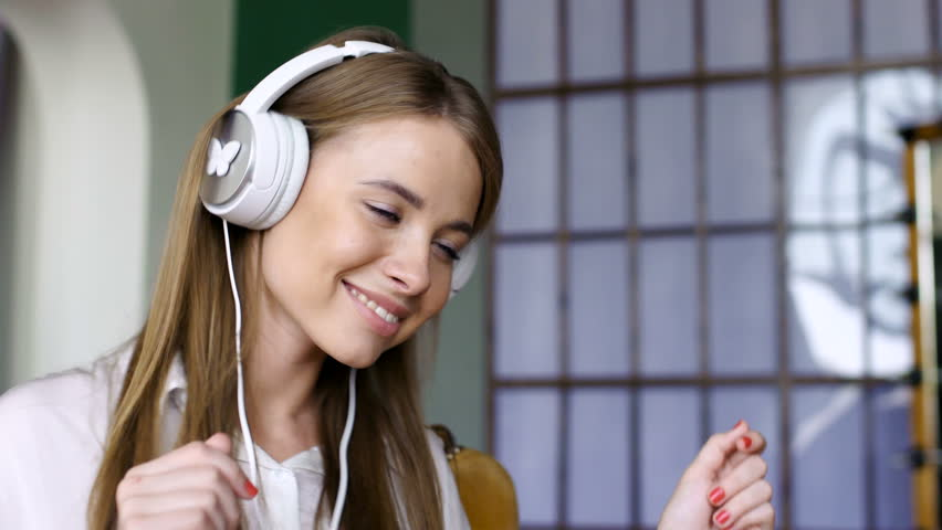 Cute teen dancer wearing white headphone and listening. Energetic dance with laugh and smile of pleasure. Close up indoors. Brunette 20s with long straight hair and fresh skin shaking head, motion | Shutterstock HD Video #19344685