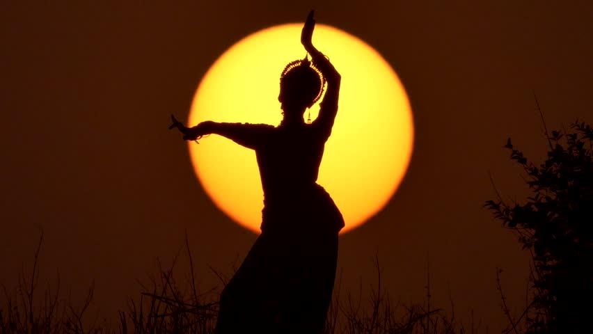 Silhouette girl oriental dancer a dance on sunset