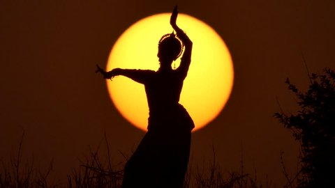 Silhouette girl oriental dancer a dance on sunset