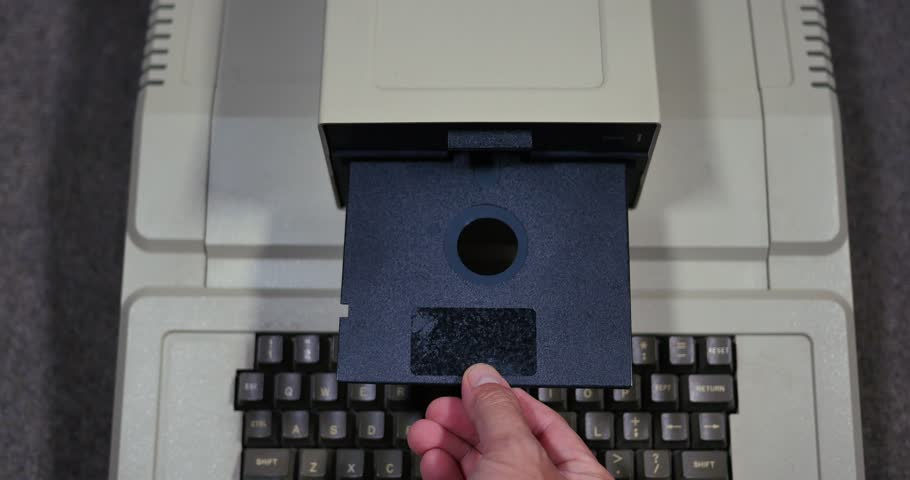 Overhead shot of someone inserting and removing an old-style 5.25-inch floppy disk. Shallow depth of field.