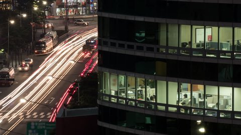 Timelapse shot of night car traffic with modern office business centre in foreground, people working in the office can be seen through the windows. Seoul, South Korea