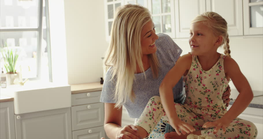 Loving mother and daughter. Mother tickling little girl on kitchen table