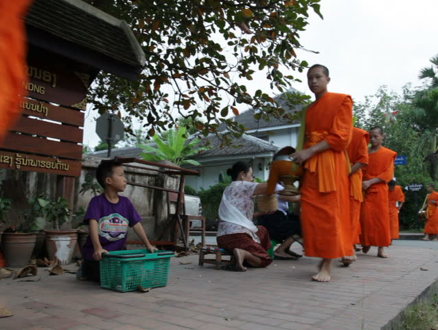 LUANG PRABANG, LAOS - OCTOBER 27: Two women give sticky rice to monks during the morning procession on October 27, 2011.