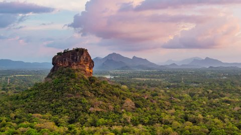 View of people going down the Lion Rock in Sigiriya, Sri Lanka. Aerial view of the tropical forest with mountains. Time-lapse of sunset sky