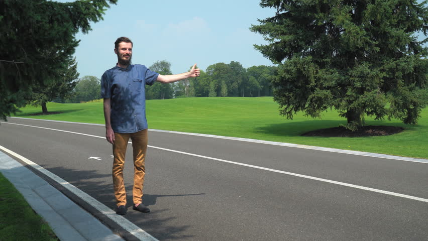 Young man traveling hitchhiking. Hitchhiker use hand signal point thumb up. Handsome guy stand near the road and waiting for some car. Caucasian traveler wearing in casual dress on the route.