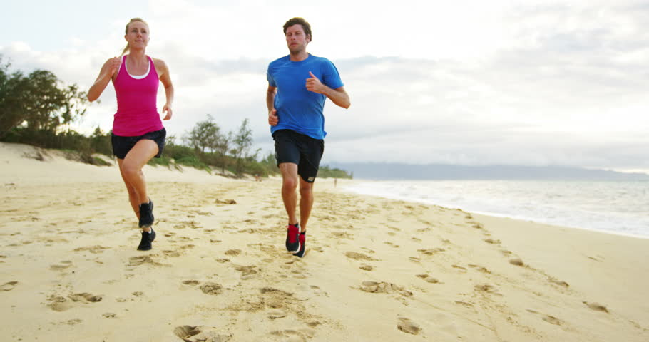 Athletic Couple Jogging Together On The Beach At Sunset 4k Stock Clip