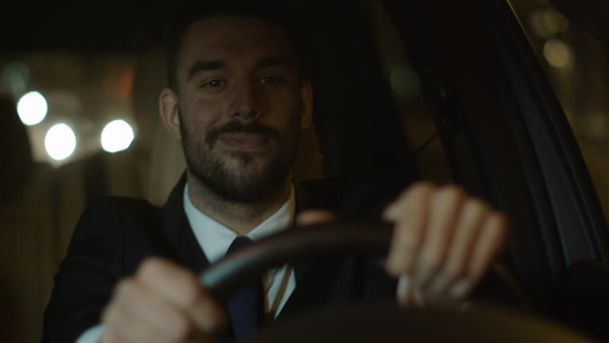 Happy Smiling Businessman Driving a Car through Streets of Night City. Shot on RED Cinema Camera in 4K (UHD).