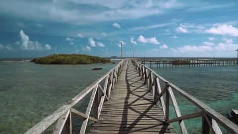 Moving forward on boardwalk in ocean, small island in front - on Siargao Island, Philippines