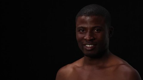 Happy toothy smiling naked black man posing in studio for photographer. Attractive sexy man with short haircut looking at camera over black background.