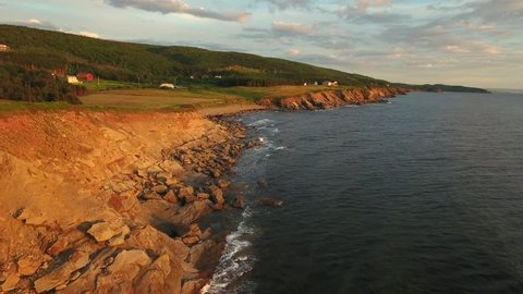 An aerial shot of a beautiful sunset on the coastline over the ocean in Cape Breton island Nova Scotia Canada
