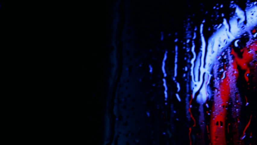 A pan across glowing neon open sign seen through a rain splattered window