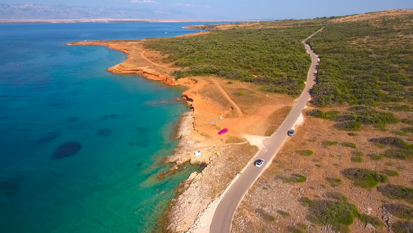 Flying over Vir island with beautiful wild beaches 4K. Aerial view of car driving on road beside the sea with view on beaches and coast on a sunny day. Beauty of Croatia.