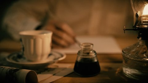A man writing with a dip ink pen lit by the light from an oil lamp.