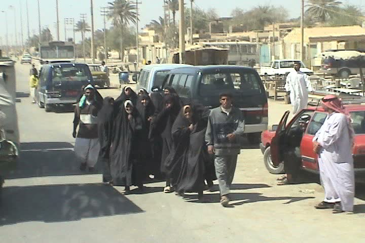 BAGHDAD, IRAQ - CIRCA 5/1/03: Iraqi women in burkas waving while men greet one another.