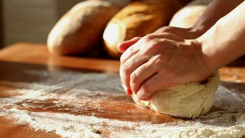 Baker hands kneading dough in flour on table, slow motion