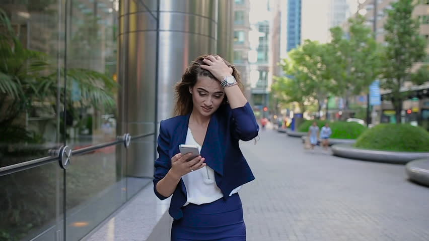 The Girl in a Blue Jacket With Her Hair Goes in the Alley Next to the Building With High Windows. Woman Talking on the Phone. | Shutterstock HD Video #19552657