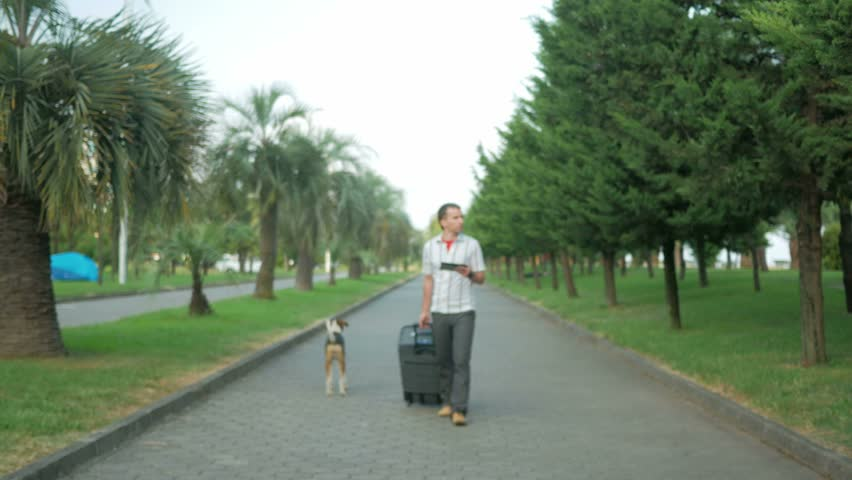 Young man tourist is with a large suitcase on wheels around the city park. In the hands of a tablet with a tablet and is looking for the right road. Nearby walks stray dog. | Shutterstock HD Video #19589047
