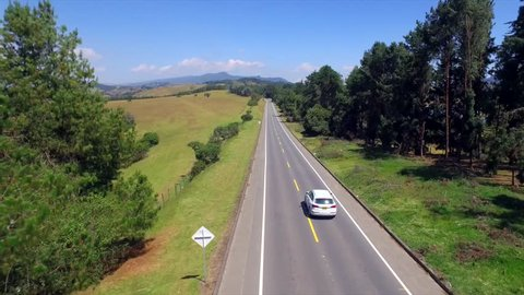 aerial view of a white car passing on a highway between landscape