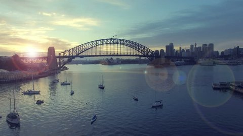 4k aerial footage b-roll of Sydney Harbour Bridge during sunrise at summer. Cinematic look and lens flare effect.