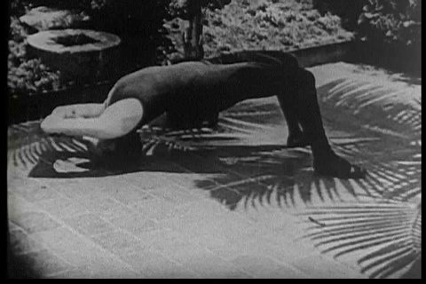 A young woman does breathing and bending exercises to help prevent constipation in the 1920s. (1920s)