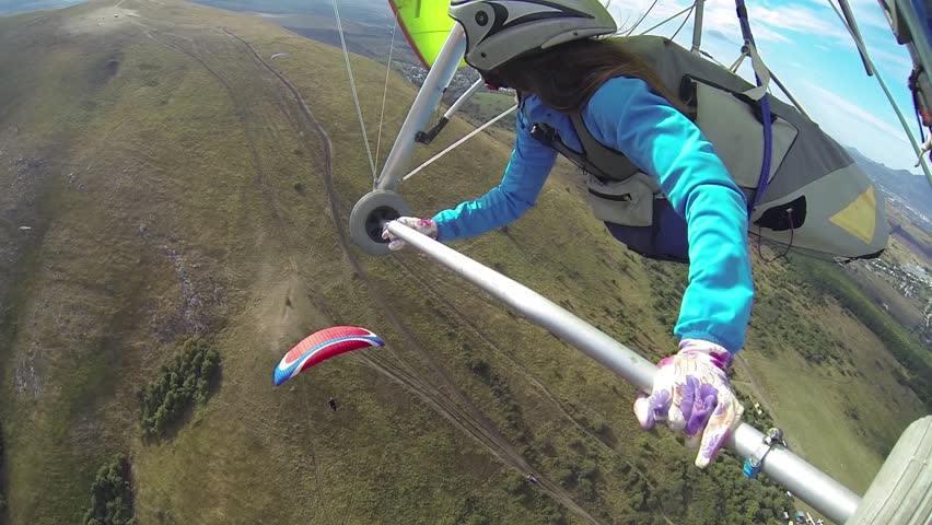 Woman on a hang glider flying over the paraglider. View from the hangglider. Shooting with on-board GoPro camera.