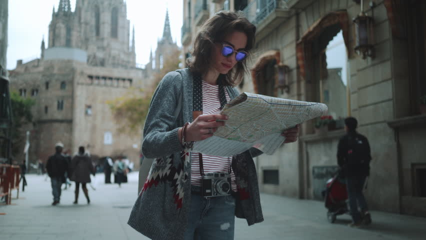 Vacation and travel concept, Young happy woman traveling at Spain and looking Barcelona landmarks, hipster girl with map at the city center, slow motion, urban scene