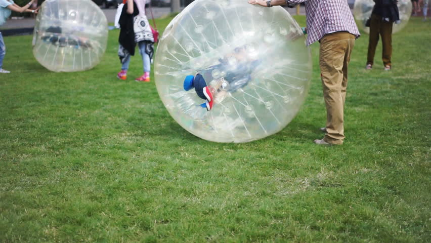 Kids and parents rolling inside hamster zorb balls, picnic in park, summertime