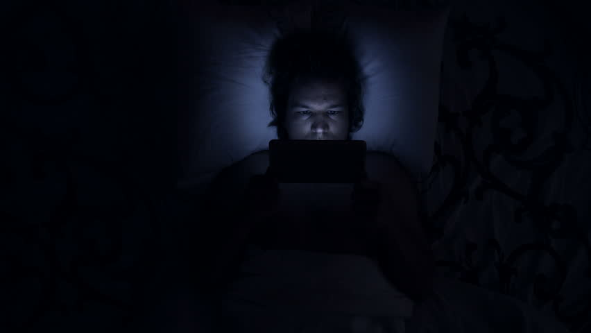 Man uses tablet computer in bed. Watching movies or going on social media, using a device before sleep with insomnia or sleeplessness. Causes are shining blue light or internet addiction.