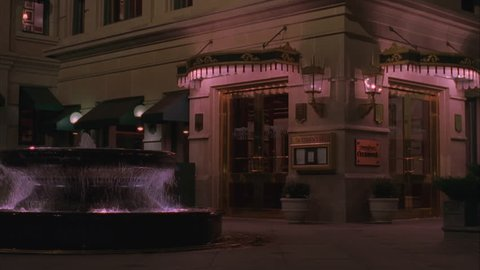 night Raked right upscale bar restaurant w glass doors fountain out front, could be older ornate hotel entrance Woman thru
