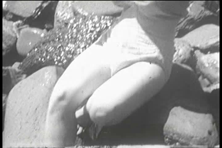 1950s pin-up girl/model Adele Dolman tries to sit on the rocks of a beach while the waves come in, but her bikini top slips a few times in the process. (1950s)