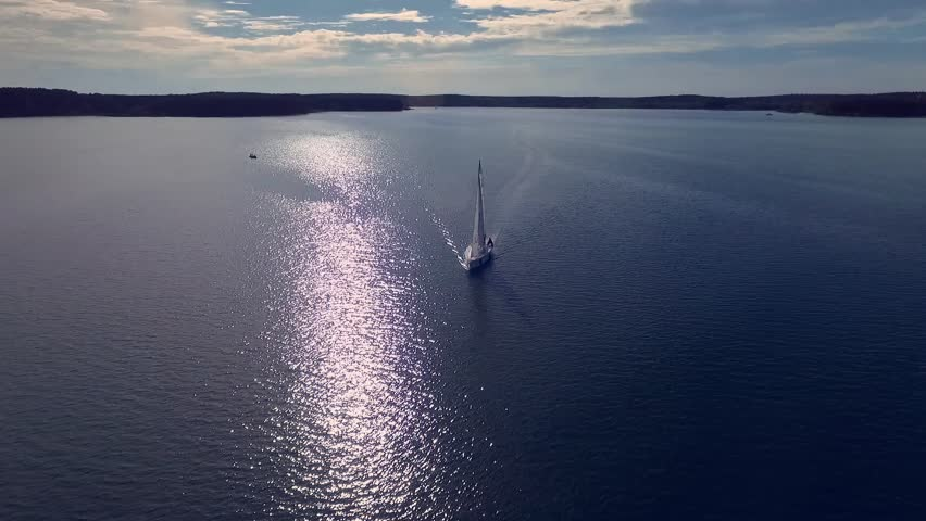 Lonely white yacht, which is floating in the rays of the sun. Shooting with the drone. Blue water. | Shutterstock HD Video #19761667