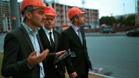 4k. UHD. Construction worker with digital pad and businessmen in suit and protective helmets talking on site about new construction. Crane and beams at the background. Teal and orange middle stabicam