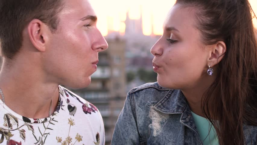 Young loving couple blowing bubblegum candy bubbles on a rooftop in the city at sunset. Slow motion