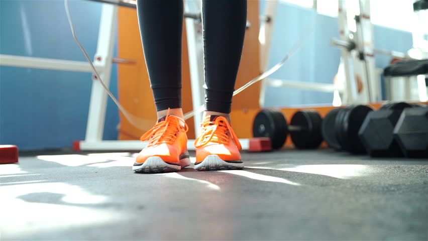 A woman in sport orange outfit jumps the rope inside in the gym 20s. 1080p Slow Motion