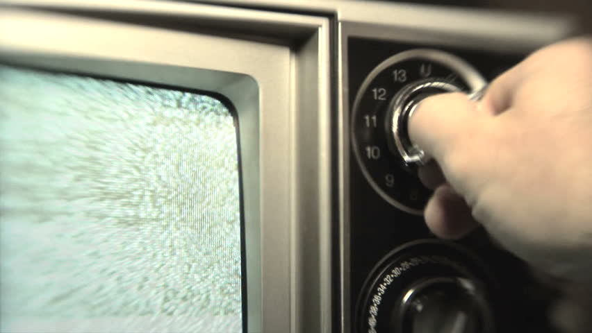 Static TV, Man (30s) turning channel knob on retro television stuck on static