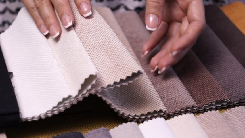 Female hands choosing fabric stitched upholstery